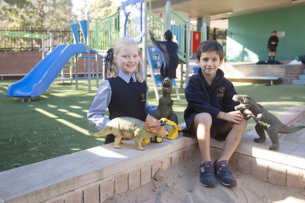 students playing with dinosaurs at school playground