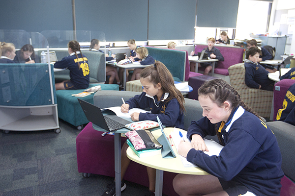 students with their devices doing school work
