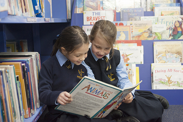students reading a book in the library